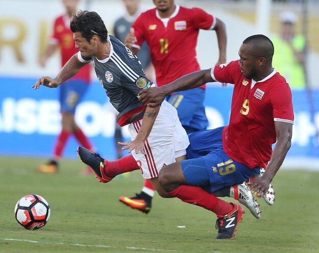 Kostarický obranca (vpravo) videl v nadstavenom čase červenú kartu za tento zákrok.