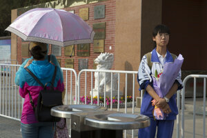 Študentka s kvetmi čaká po skončení skúšky na príbuzných.
