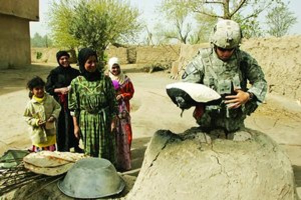 Iračanka sleduje britského vojaka, ako pečie chlieb.