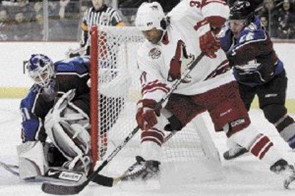 Brankár Colorada Peter Budaj zneškodňuje šancu útočníka Phoenixu Georgesa Laraqueho (v bielom), ktorému sa zozadu snaží vypichnúť puk Paul Šťastný. V zápase NHL v Denveri vyhral domáci tím Avalanche nad Coyotes 4:3.