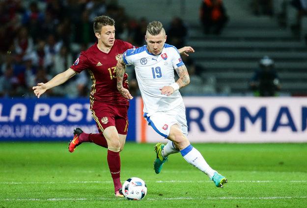 Juraj Kucka (vpravo) sa v zápase s Ruskom pokúša s loptou obísť Aleksandra Golovina.