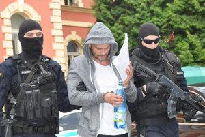 """Policajní kukláči predviedli na súd v Banskej Bystrici desať obvinených zo skupiny podsvetia zvaných """"piťovci""""."""