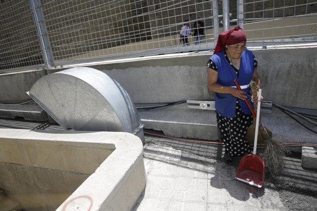 Žena čistí plot pri novej trati.