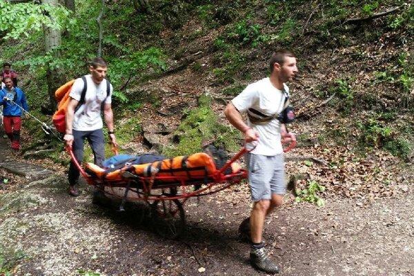 Horskí záchranári znášajú zraneného turistu pomocou rakúskeho vozíka.
