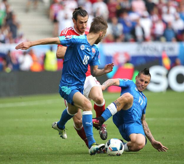 Marek Hamšík (vpravo) prestrkáva loptu na Dušana Šventa (s číslom 18). Zastaviť akciu Slovenska sa snaží Gareth Bale.