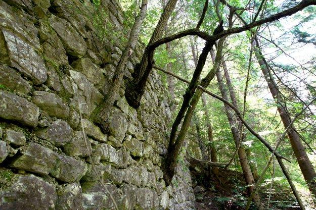 Pozostatok banského múru susedí s jazierkom.