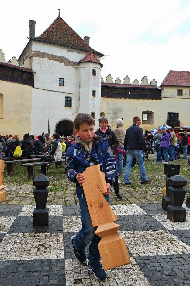 Kežmarský hrad. Chlapec ťahá drevenou figúrkou po veľkej šachovnici na hlavnom nádvorí hradu počas otvorenia letnej sezóny 2015.