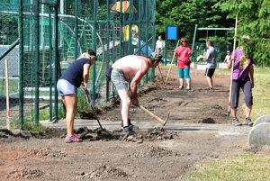 Brigáda. Bez dobrovoľníkov by dráha ďalej zarastala trávou.