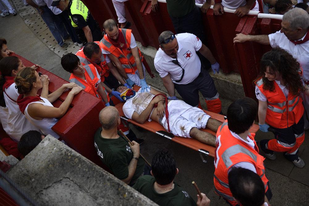 Zdravotníci odnášajú zraneného muža počas druhého tohtoročného behu pred býkmi.