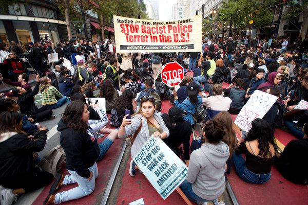 Ľudia pochodujú počas protestu proti zastreleniu dvoch Afroameričanov.
