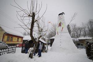 Obrovský snehuliak stojí na dvore rodinného domu