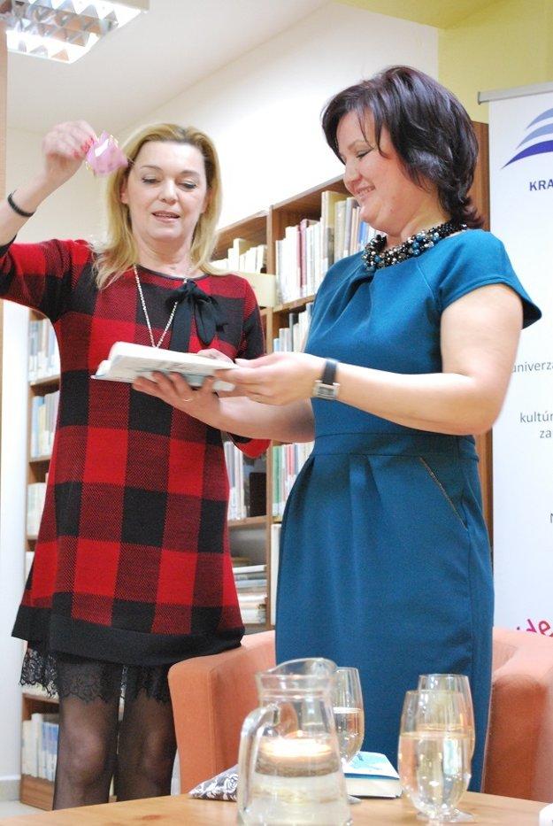 Daniela Kuffelová (vľavo) krstí Zuzaninu knihu zrnkami kávy.