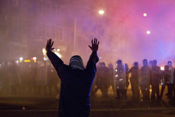 Demonštrant stojí zoči-voči polície počas nepokojov v uliciach Baltimoreu po pohrebe Afroameričana Freddieho Graya v americkom Baltimore.