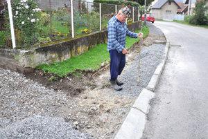 Štefan Adamec rozhŕňa štrk pod asfalt.