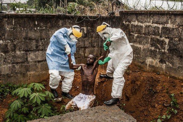 Zdravotníci odvádzajú utečenca nakazeného vírusom späť do karantény v Hastingsu, Sierra Leone.