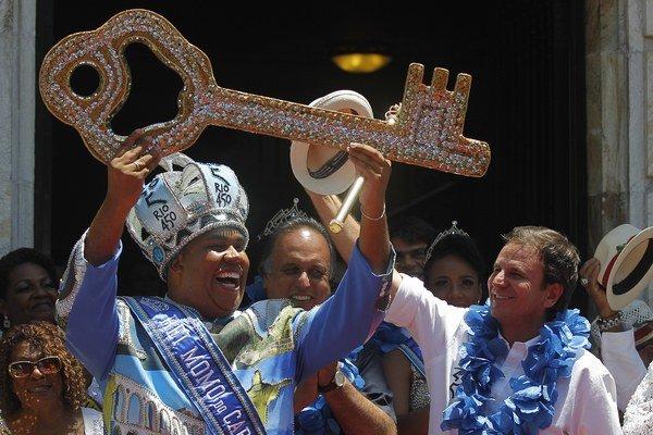 Tohtoročný karnevalový kráľ - kráľ Momo (vľavo) preberá od starostu mesta Rio de Janeiro Eduarda Paesa (vpravo) kľúč od mesta počas úvodných osláv svetoznámeho karnevalu v Riu de Janeiro 13. februára 2015. Kráľ Momo je mýtická postava, ktorá vládne Riu po