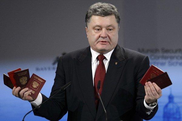 Ukrajinský prezident Porošenko ukazuje ruské pasy počas prejavu na mníchovskej konferencii.