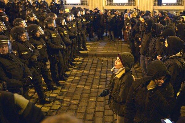 Policajti stoja pred účastníkmi akcie PEGIDA.