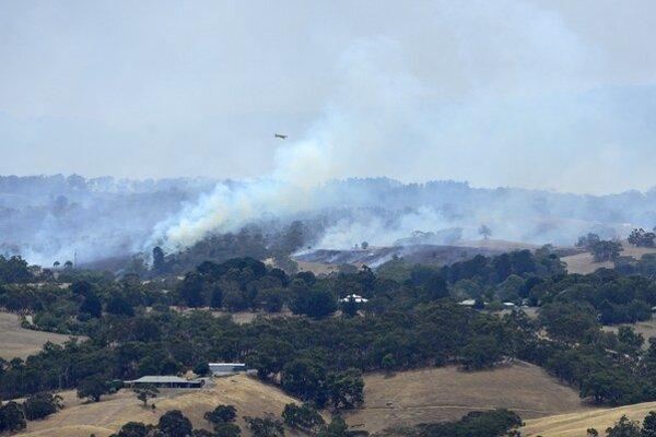 Lietadlo letí nad dymom z požiarov v okolí austrálskeho mesta Adelaide 3. januára 2015.