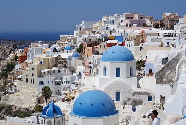 Santorini je obľúbená destinácia najmä pre modré kupoly kostolíkov uprostred bielych a okrových domov v dedinke Oia.