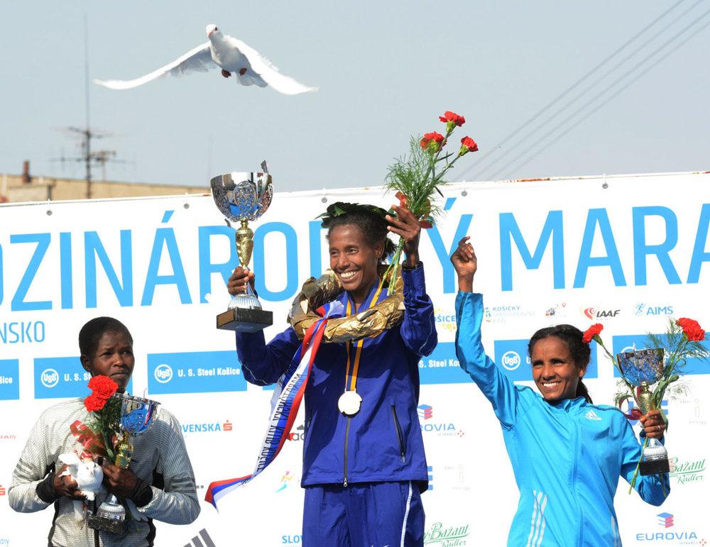 Tri najlepšie ženy s kyticami, pohármi a bielou holubicou mieru nad hlavami. Typický obrázok po dekorovaní víťazov.