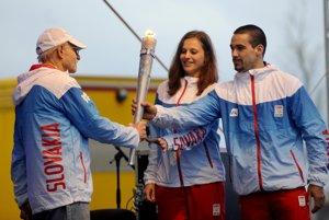 Ján Matocha (vľavo) odovzdáva olympijský oheň v Londýne Danke Bartekovej a Samuelovi Piaseckému.