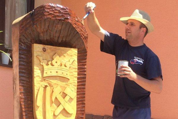 Starosta si zamenil prácu vúrade za natieranie lipovej sochy svyrezaným erbom obce, ktorá stojí pri vstupe do obce.