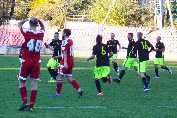 Iľja Čeredničenko (na snímke medzi dvoma hráčmi B. Bystrice) sa teší z víťazného gólu v nadstavenom čase.
