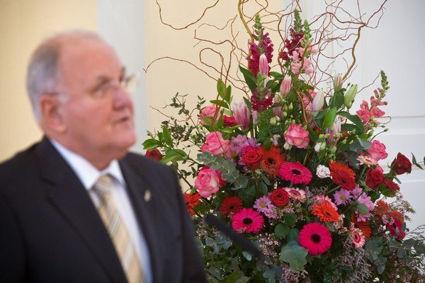 Minister školstva Dušan Čaplovič, v pozadí kvetinová výzdoba.