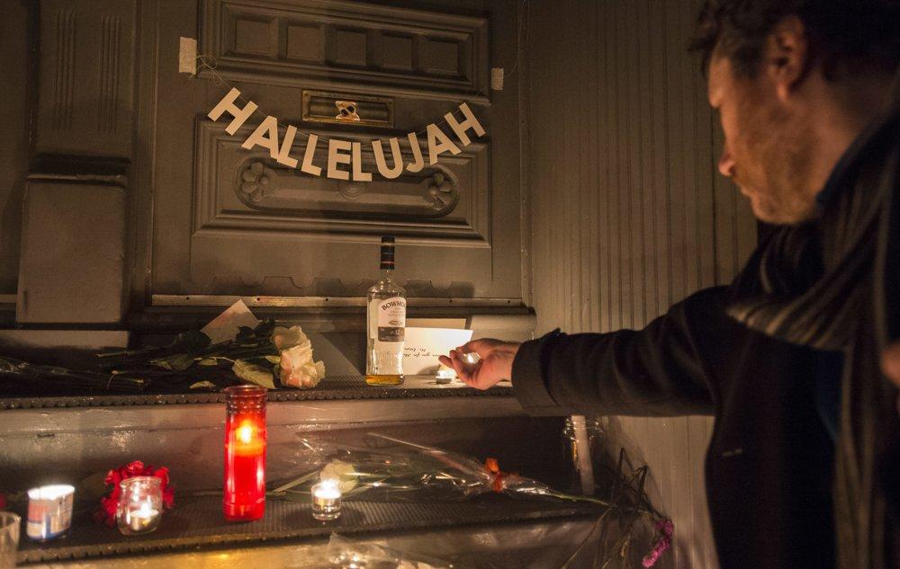 Fanúšik zapaľuje  sviečku pred dom zosnulého speváka Leonarda Cohena v kanadskom meste Montreal. FOTO - TASR/AP