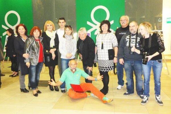 Desiati z 12 členov APF klubu pózujú pred svojou výstavou v OC Centro, dolu kurátor výstavy Daniel Brogyáni.
