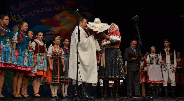 Mária Lisoňová prináša dieťa do rúk kňaza.