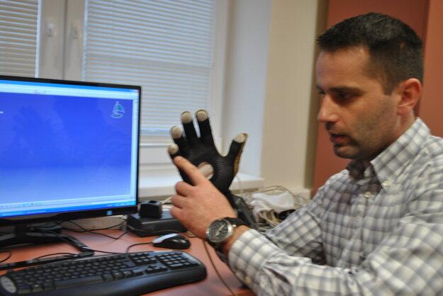 Robotická rukavica. Vedci v experimentálnom laboratóriu virtuálnej a zmiešanej reality skúšajú robotickú roku, ktorá má v budúcnosti pomáhať najmä v nebezpečnom a zdraviu škodlivom prostredí. Na snímke odborný asistent Juraj Kováč.