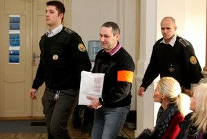 Sergej v sprievode stráže na ceste pred súd.
