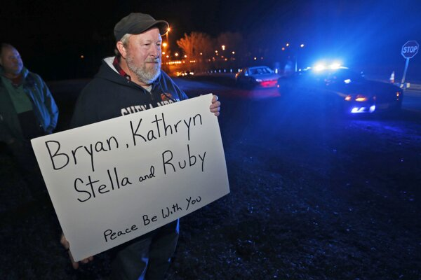 Muž na pamiatku obetí drží transparent s menami rodiny Harveyovcov.