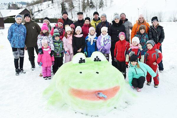 Tvorcovia snehových sôch s maskotom dediny - žabou.