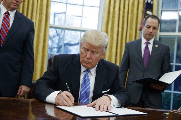 Americký prezident Donald Trump podpisuje výkonné nariadenie o odstúpení USA od Dohody o transpacifickom partnerstve (TPP) s 11 štátmi Tichomoria v Oválnej pracovni Bieleho domu vo Washingtone.