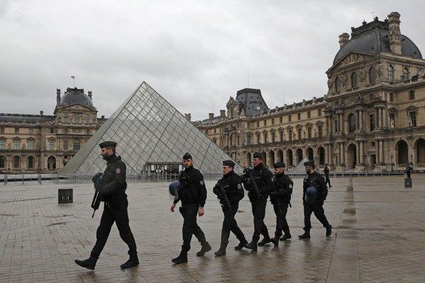 Hliadkujúci policajti pred múzeom v Louvri.