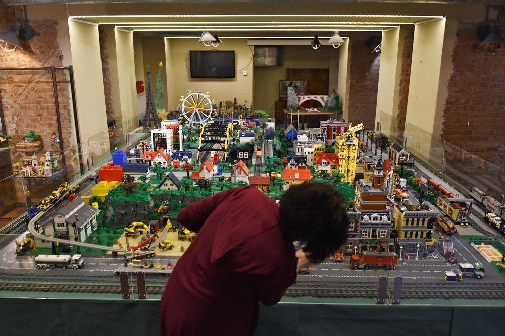 Pracovníčka galérie pripravuje diorámu postavenú z kociek stavebnice Lego.