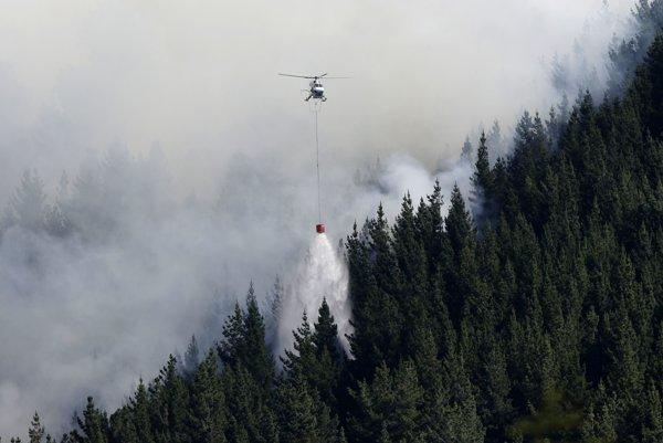 Požiarne vrtuľníky zasahujú proti ohňu.