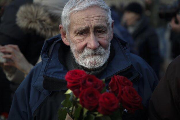Starší muž s ružami na pamiatku Borisa Nemcova.