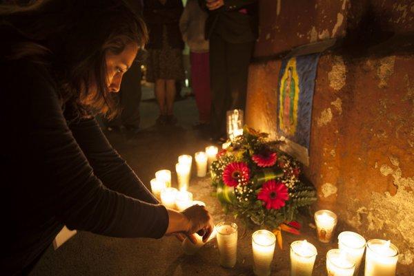 Žena zapaľuje sviečku počas spomienkovej omše za obete požiaru.
