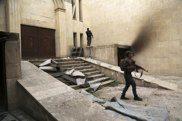 Irackí federálni policajti hliadkujú pred zničenou budovou múzea počas bojov v západnej časti irackého mesta Mósul.