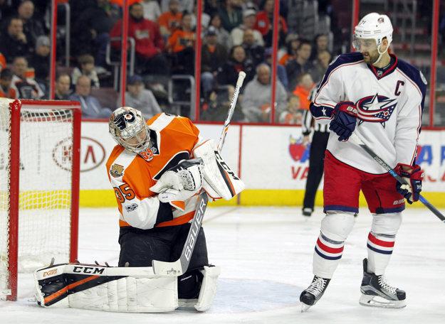 Brankár Philadelphie Steve Mason (vľavo) zasahuje pred cloniacim Nickom Folignom.