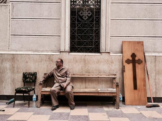 Muž sedí na lavičke kostola po bombovom útoku.