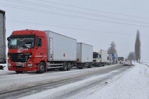 Kamióny a nákladné autá stoja v kolóne v silnom snežení a vetre na ceste I/18 medzi Popradom a Hôrkou.