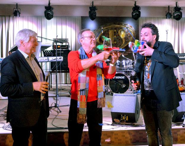Krstní otcovia. Pestrofarebnými pierkami nový album pokrstili textár Ľuboš Zeman a muzikant Marián Čekovský.