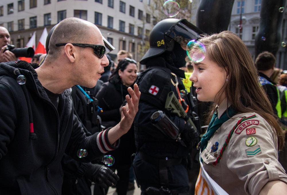 Fotografia 16-ročnej skautky Lucie Myslíkovej a extrémistu vznikla v Brne počas prvomájového protestu Kdo si hraje, nehajluje. Účastníci sa hravou formou snažili blokovať neonacistický pochod.