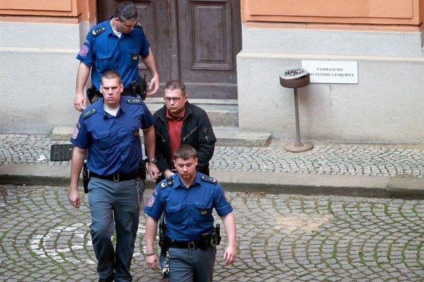 Ján Bakalár v sprievode polície.