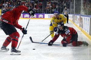 Mitch Marner (s číslom 16) padá na ľad pri súboji o puk s Eliasom Lindholmom (v žltom drese).